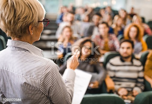 Back view of a senior professor talking on a class to large group of students.