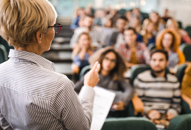 Rear view of mature teacher giving a lecture in a classroom. Back view of a senior professor talking on a class to large group of students. showing stock pictures, royalty-free photos & images