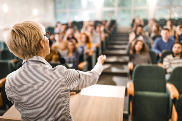Rear view of mature teacher giving a lecture in a classroom. stock photo
