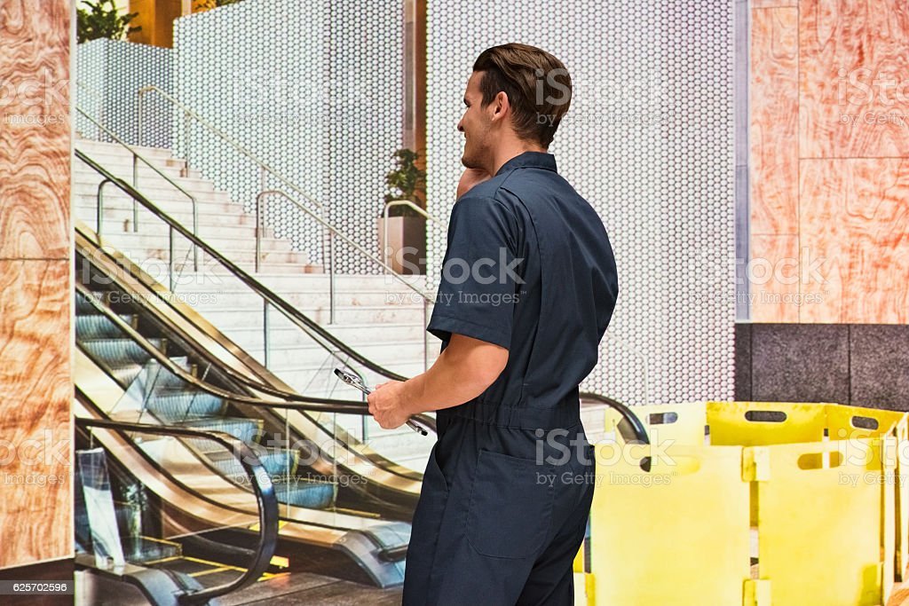 Rear view of mechanic on phone in office stock photo