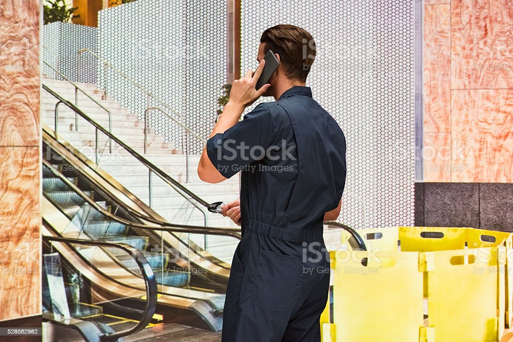 Rear view of mechanic on phone stock photo