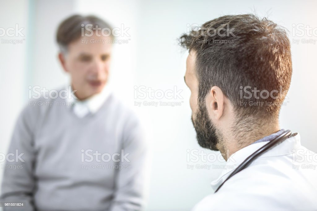 Rear view of mid adult doctor talking with senior patient. stock photo