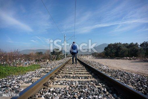 Rear view of mid-adult man walking alone on railroad