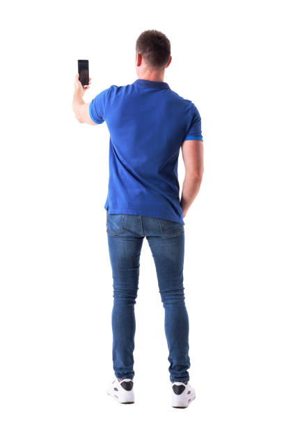 Rear view of modern adult casual man taking photo with smart phone. stock photo