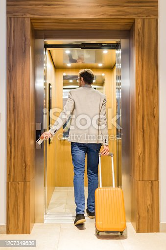 638591126 istock photo Rear view of modern man with baggage getting in hotel or office building elevator. 1207349536