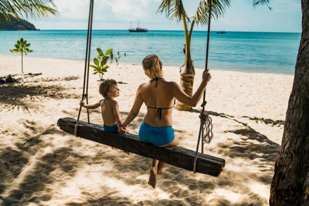 vista traseira da mãe e do filho enquanto balançando na praia de mãos dadas. - beach in thailand - fotografias e filmes do acervo