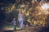 Rear view of mother and son holding hands while taking a walk in autumn park.
