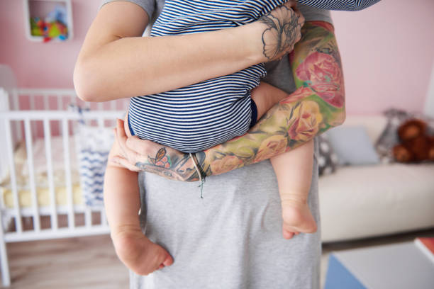 Rear view of mother carrying her son stock photo