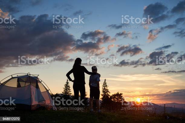 Photo of Rear view of mother hugs her son near tent on top of mountain enjoying view of sun