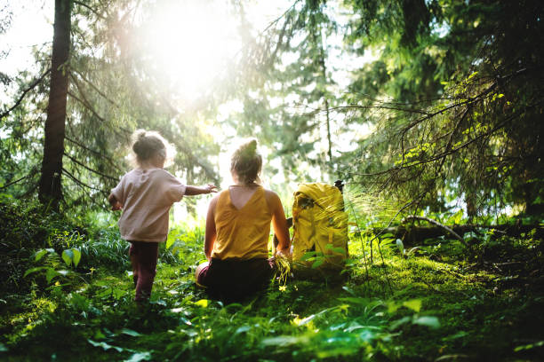 rear view of mother with small daughter outdoors in summer nature, resting. - forest bathing foto e immagini stock