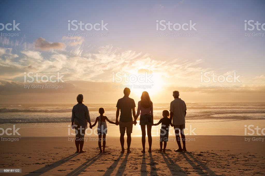 Rear View Of Multi Generation Family Silhouetted On Beach stock photo