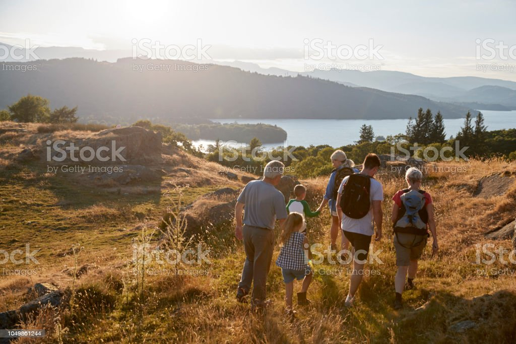 Rear View Of Multi Generation Family Walking On Top Of Hill On Hike Through Countryside In Lake District UK stock photo