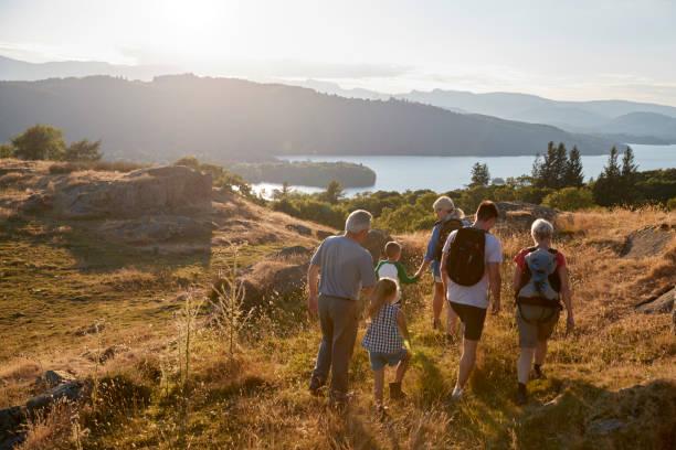 rückansicht des multi-generationen-familie zu fuß auf hügel auf wanderung durch die landschaft im lake district uk - cumbria stock-fotos und bilder
