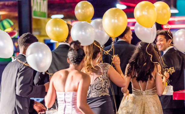 Rear view of multi-ethnic teenagers at prom Rear view of a group of multi-ethnic teenagers at prom. They are wearing prom dresses and tuxedos, indoors at night, holding gold and white balloons. prom night stock pictures, royalty-free photos & images
