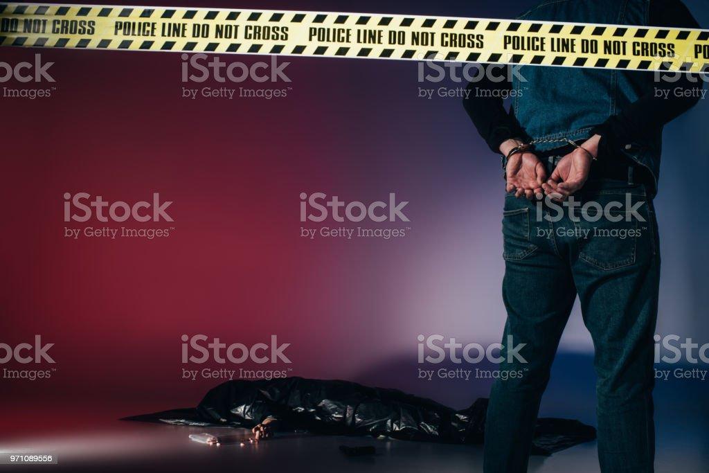 Rear view of murderer in cuffs behind police line on dark background stock photo