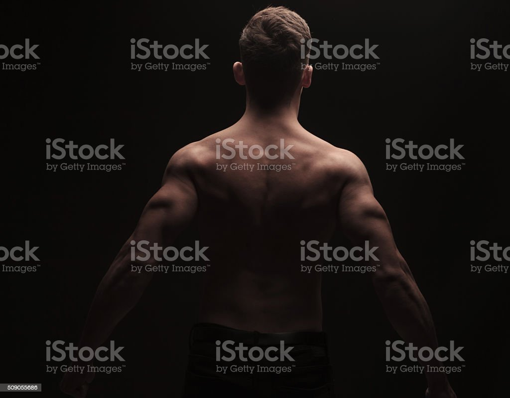 rear view of muscular man flexing his back and arms stock photo