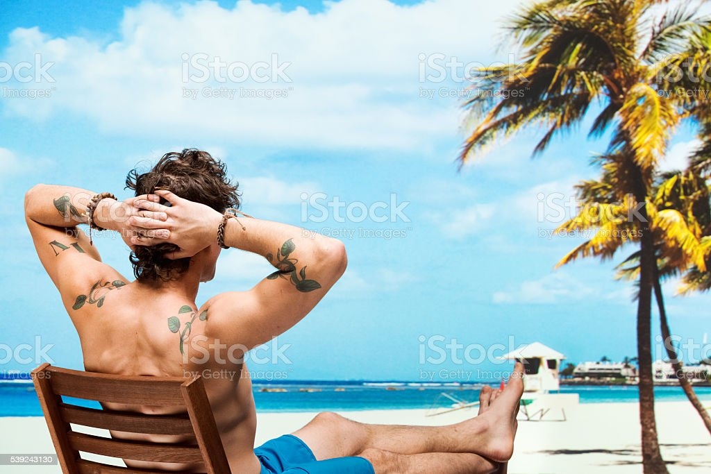 Rear view of muscular man sitting in the beach royalty-free stock photo