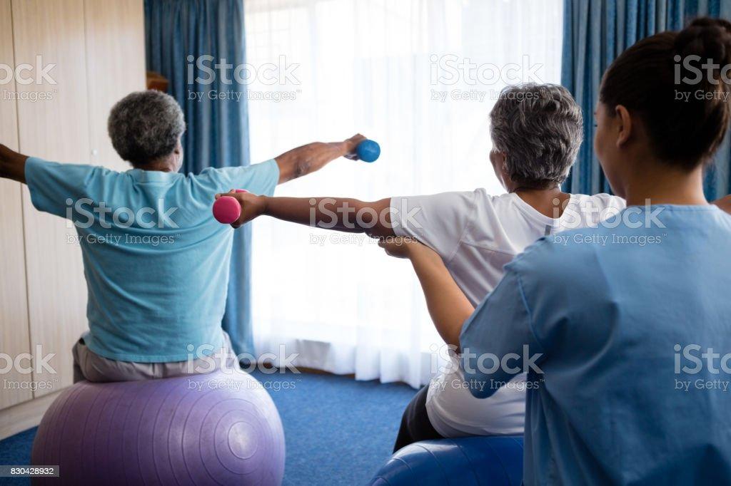 Rückansicht des Krankenschwester Ausbildung Senioren bei der Aufhebung der Hanteln – Foto