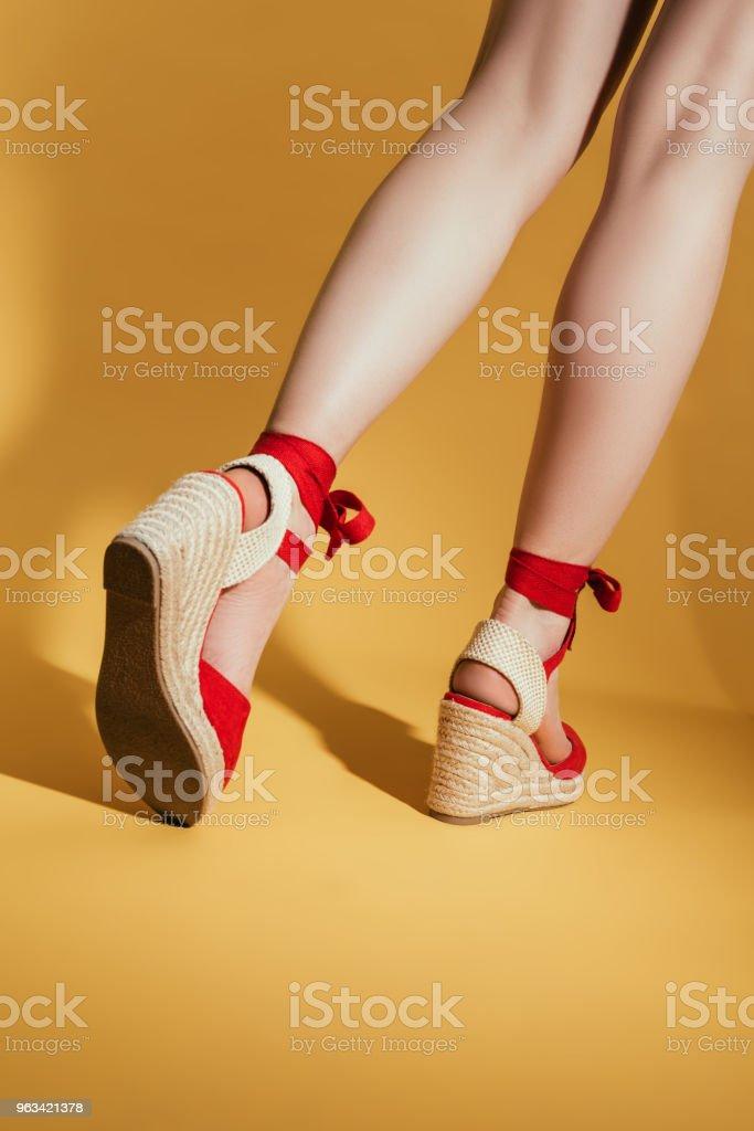 rear view of of woman legs in stylish platform sandals on yellow background - Zbiór zdjęć royalty-free (Cięcie w lini dolnej)