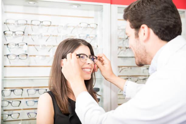 rückansicht des augenarzt helfen frau gläser im optischen speicher wählen - lieblingsrezepte stock-fotos und bilder