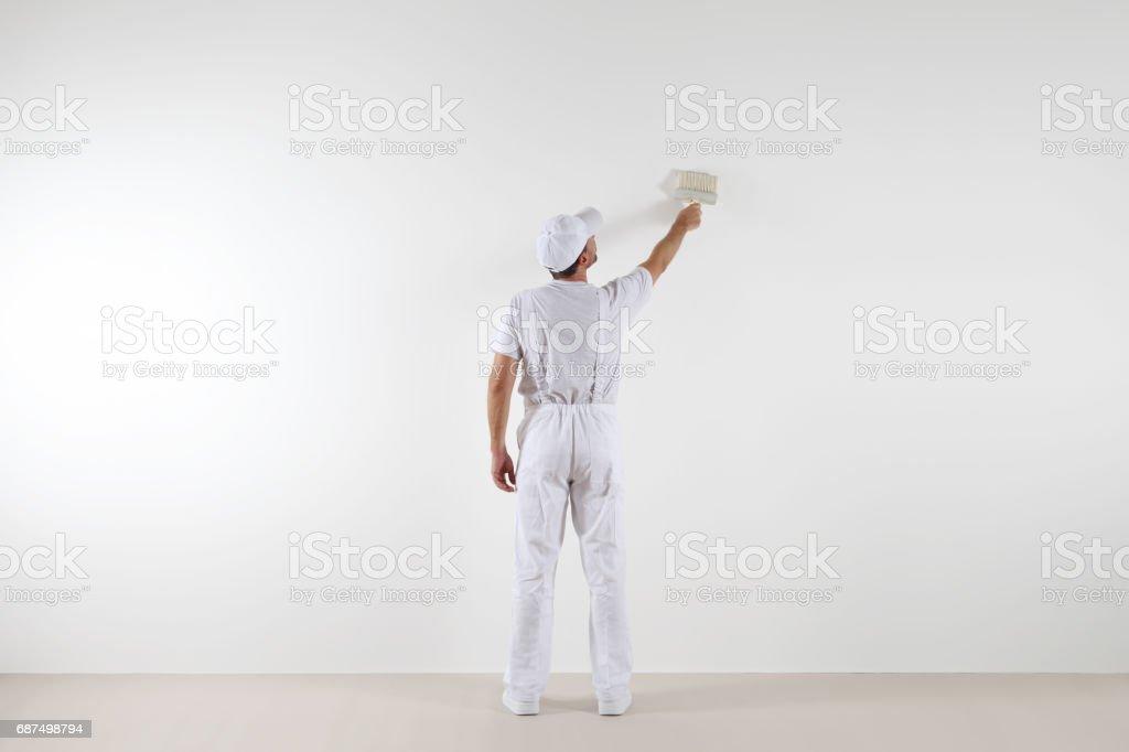 Heckansicht des Malers Mann auf der Suche und leere Wandbemalung, mit Pinsel, isoliert auf weißen großen Raum – Foto