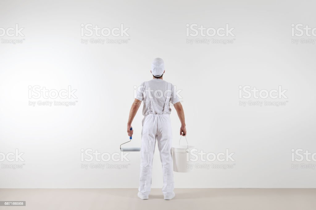 Rear view of painter man looking at blank wall, with paint roller and bucket, isolated on white room ストックフォト