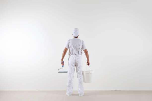 Rückansicht des Malers Mann Blick auf leere Wand, mit Farbe Rolle und Eimer, isoliert auf weißen Raum – Foto