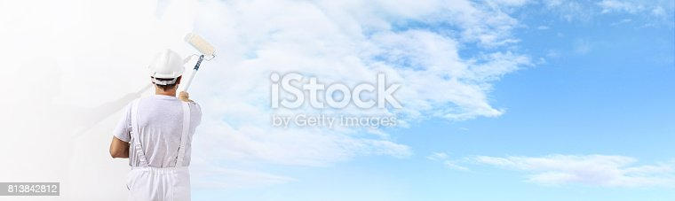 istock Rear view of painter man painting the blue sky on blank wall, with paint roller isolated on white big space panorama 813842812