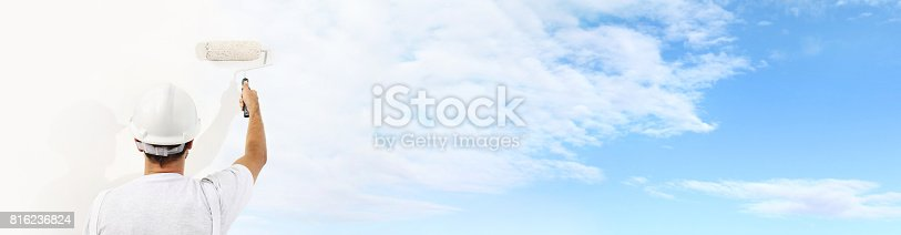 istock Rear view of painter man with paint roller painting the blue sky and clouds on blank wall, isolated on white 816236824