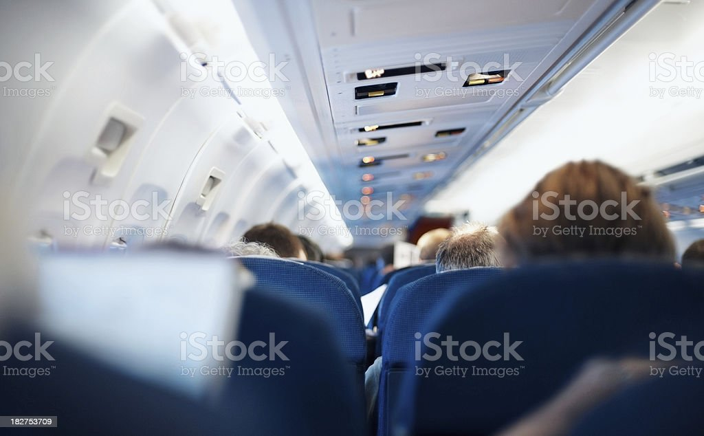 Rear view of passengers sitting in an airplane stock photo