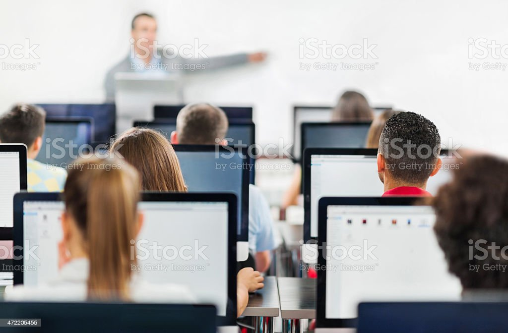Rear view of people on computers in classroom stock photo