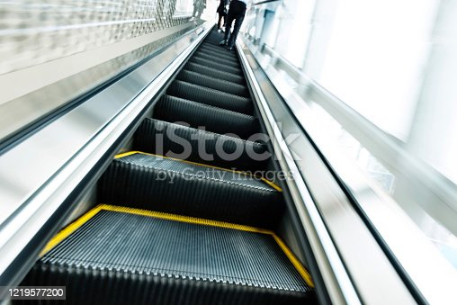 Rear view of people standing on escalator.