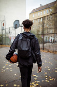 Rear view of player with basketball on street