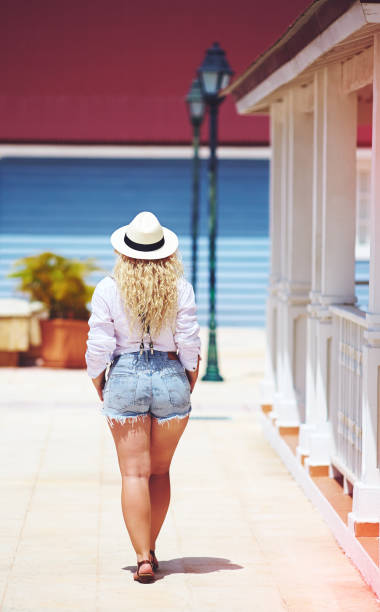 rear view of plus size woman walking on caribbean street stock photo
