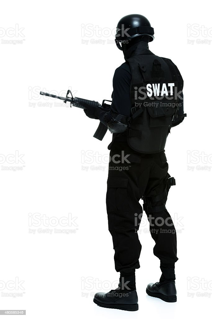 Rear view of police holding rifle stock photo