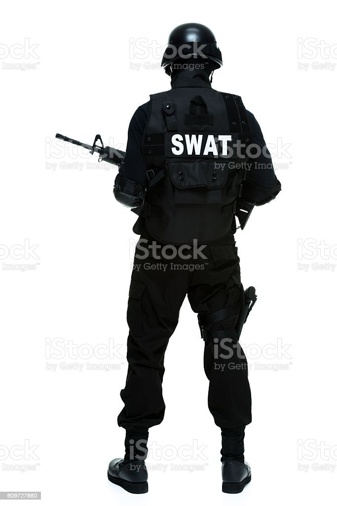 Rear view of police standing with rifle stock photo