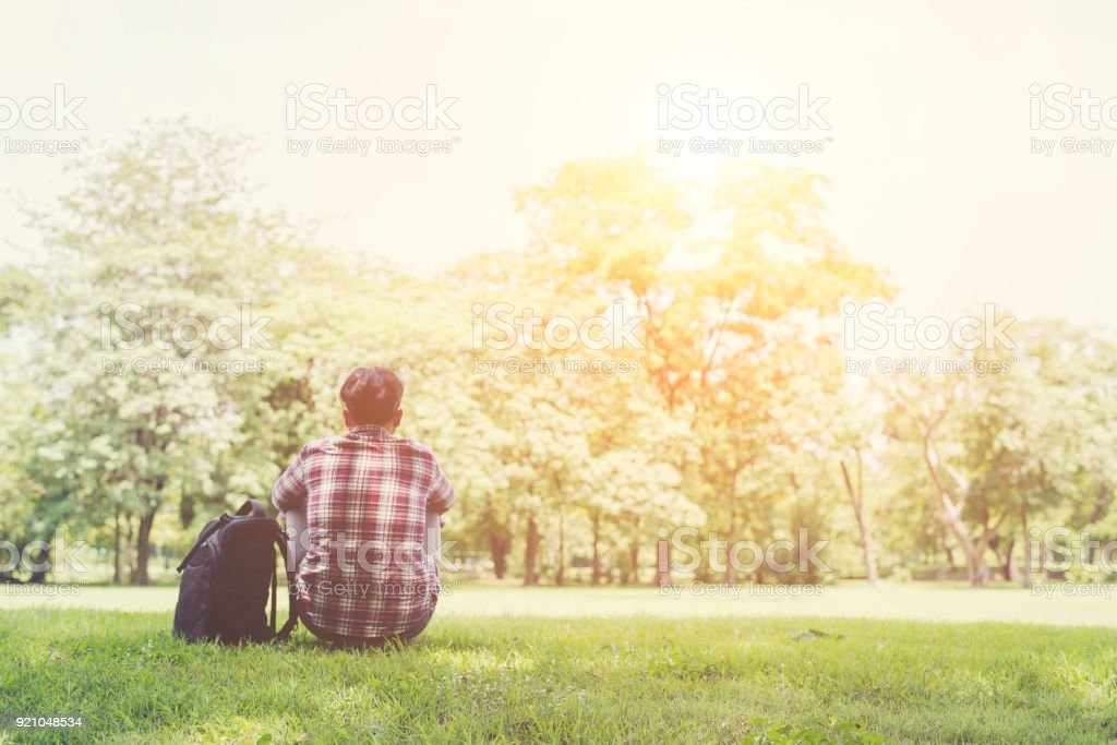 Rear view of relaxed young traveling man sitting on grass in the park behind the city. stock photo
