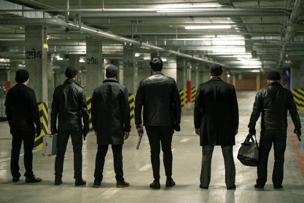 Rear view of row of criminals or gangsters in black standing on parking area stock photo