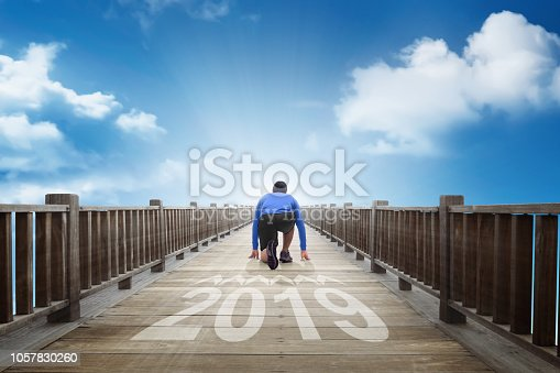 istock Rear view of runner man ready running into into year of 2019 1057830260