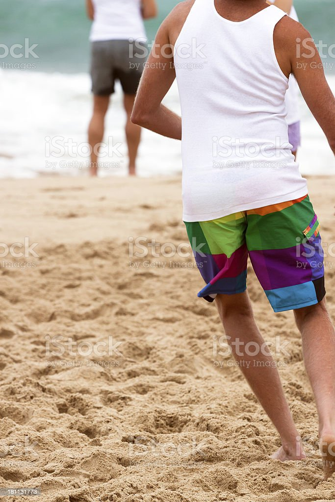 Rear view of running young male on the beach royalty-free stock photo