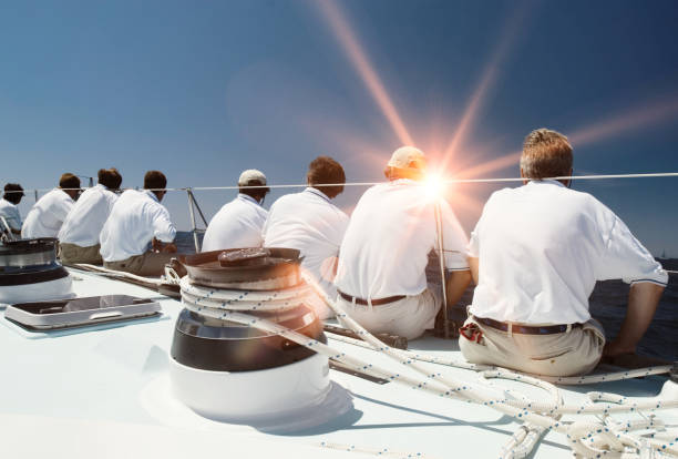 Rear view of sailing crew with lens flare stock photo