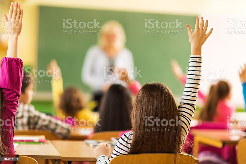 Rear view of school kids raising their hands at school. stock photo