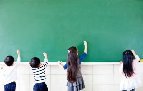 rear view of school students drawing on chalkboard stock photo