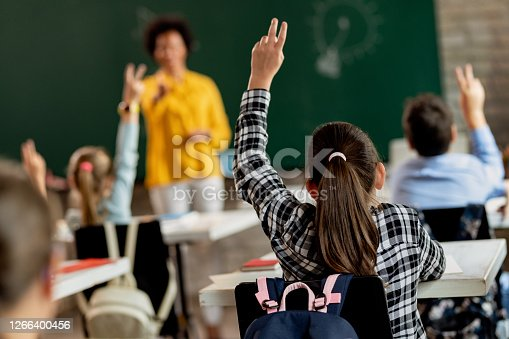 Back view of elementary student raising arm in order to answer a questing during a class.