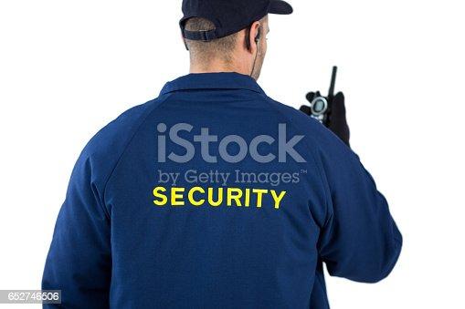 istock Rear view of security officer talking on walkie-talkie 652746506