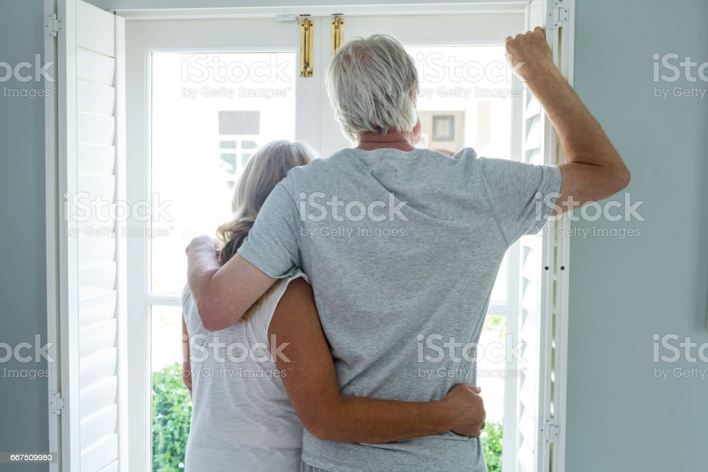 Rear view of senior couple looking through window at home foto stock royalty-free