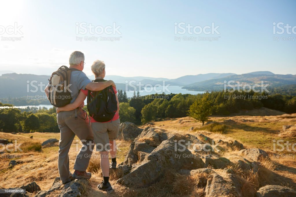 Rear View Of Senior Couple Standing At Top Of Hill On Hike Through Countryside In Lake District UK royalty-free stock photo