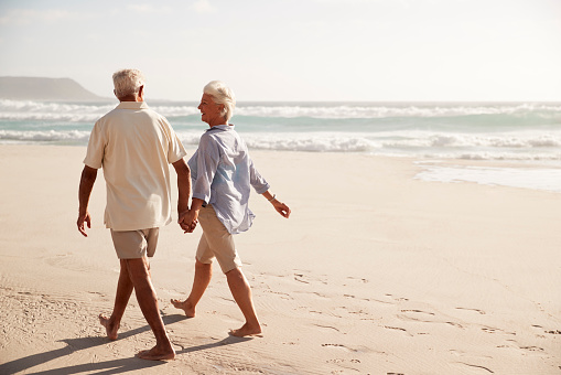 Rear View Of Senior Couple Walking Along Beach Hand In Hand
