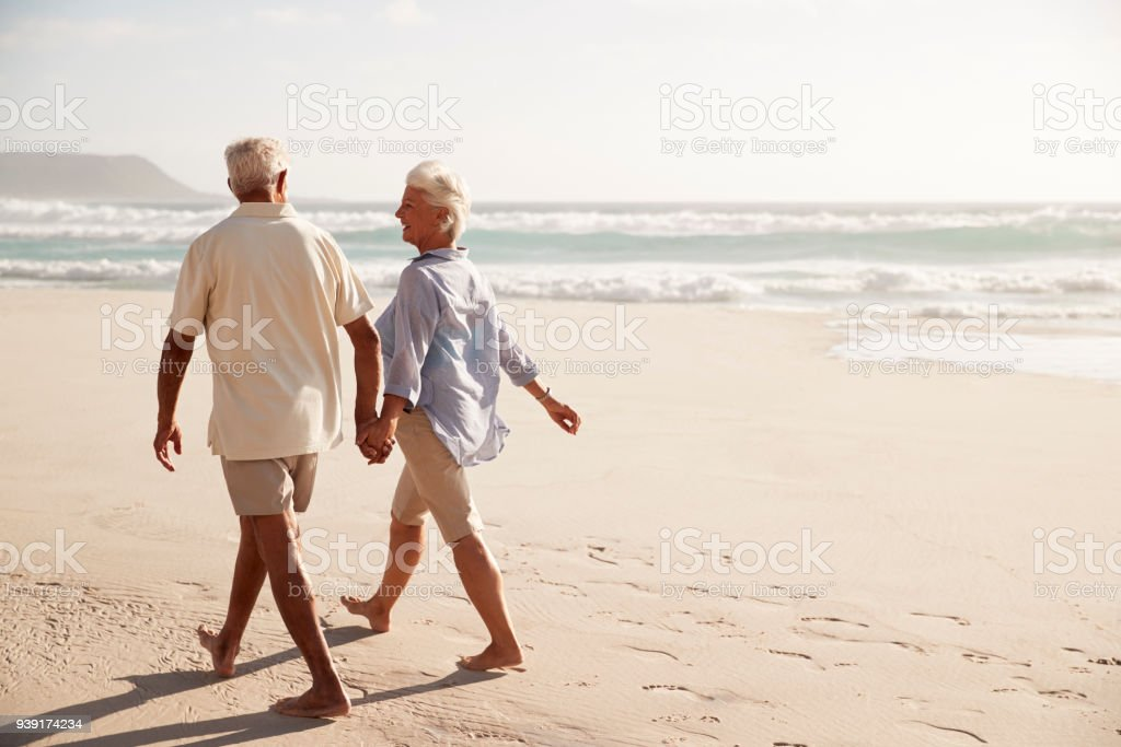 Rear View Of Senior Couple Walking Along Beach Hand In Hand stock photo
