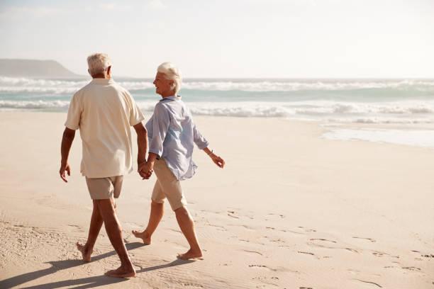 plaj boyunca el ele yürürken üst düzey çiftin arkadan görünüş - emeklilik stok fotoğraflar ve resimler